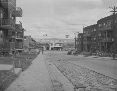 Vue du bas de l'avenue Belvédère en 1949. Ouvert dans les années 1920, il rejoint la côte Franklin. Les bâtiments qui bordent l'avenue sont de construction récente. À l'exception de l'espace commercial que l'on aperçoit au centre de la photographie, ce secteur a peu changé depuis les années 1940. (Belvedere Terrace [restaurant and garage, Quebec, P.Q.], 23 June, 1949, William B. Edwards, BAC, fonds non identifié, MIKAN no 3382788)